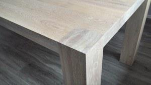 Hoek van een houten eetkamertafel